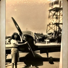 Guessing Mom is standing in front of either Dad or Uncle Charley's plane.