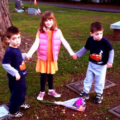 Olga's kids, Loukas, Tessa Eleni and Constantine, lay flowers on Lily's resting place on the anniversary of their grandma's loss.