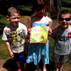 Remembering their grandma, Sean and Olga's kids Constantine, Tessa Eleni and Loukas visit Lily's final resting site with a hand-made Happy Birthday sign.