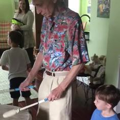 Sam showing great-grandsons Aiden and Caleb how to play