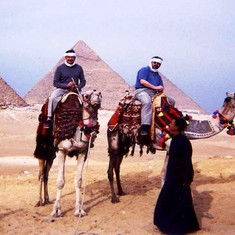 John at the Pyramids riding a camel.