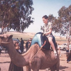 John riding a camel as a child. His father bestowed a love and appreciation for travel.