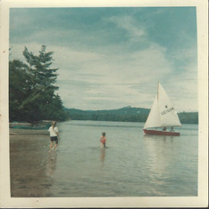 Dad manning the rudder of our Flying Tern sailboat in this picture at Lake Winnipesaukee, evidencing another of the many interests he picked up and embraced throughout his life. Mom is in the boat, Lynn and Sara wading toward our parents. Probably 1965.