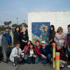 Group shot of decorative arts classmates who each created ceramic pieces to make this mosaic in Susan's honor.