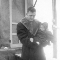 Tom and Peggy in front of basement home, December 1952