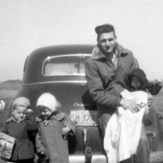 Tom with Mark, Peggy and Colleen, on road in front of Mendota home, 1956