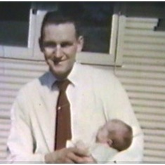Tom holding baby Shannon at the 'Huts,' St. Thomas College, summer 1957 (still from family movie)