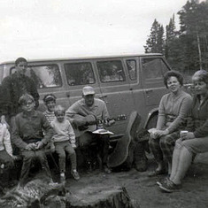 August 1967, Tom playing guitar at campfire at Grand Marais (seated: Kevin, Mark, Patty, Tom, Bev, Donna Johnson; standing: Jerry Evans, Jr., Steve Johnson))