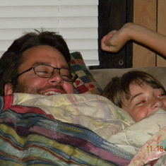 "Matthew's favorite place to be is snuggled up with dad in the ""snuggler"" watching TV."