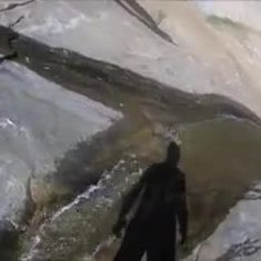 Tom slides down the waterfall